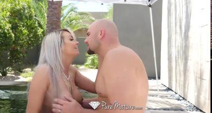 Лысый мужик возле пальмы трахает сисястую блондинку в глотку и пальцами мнет ее киску
